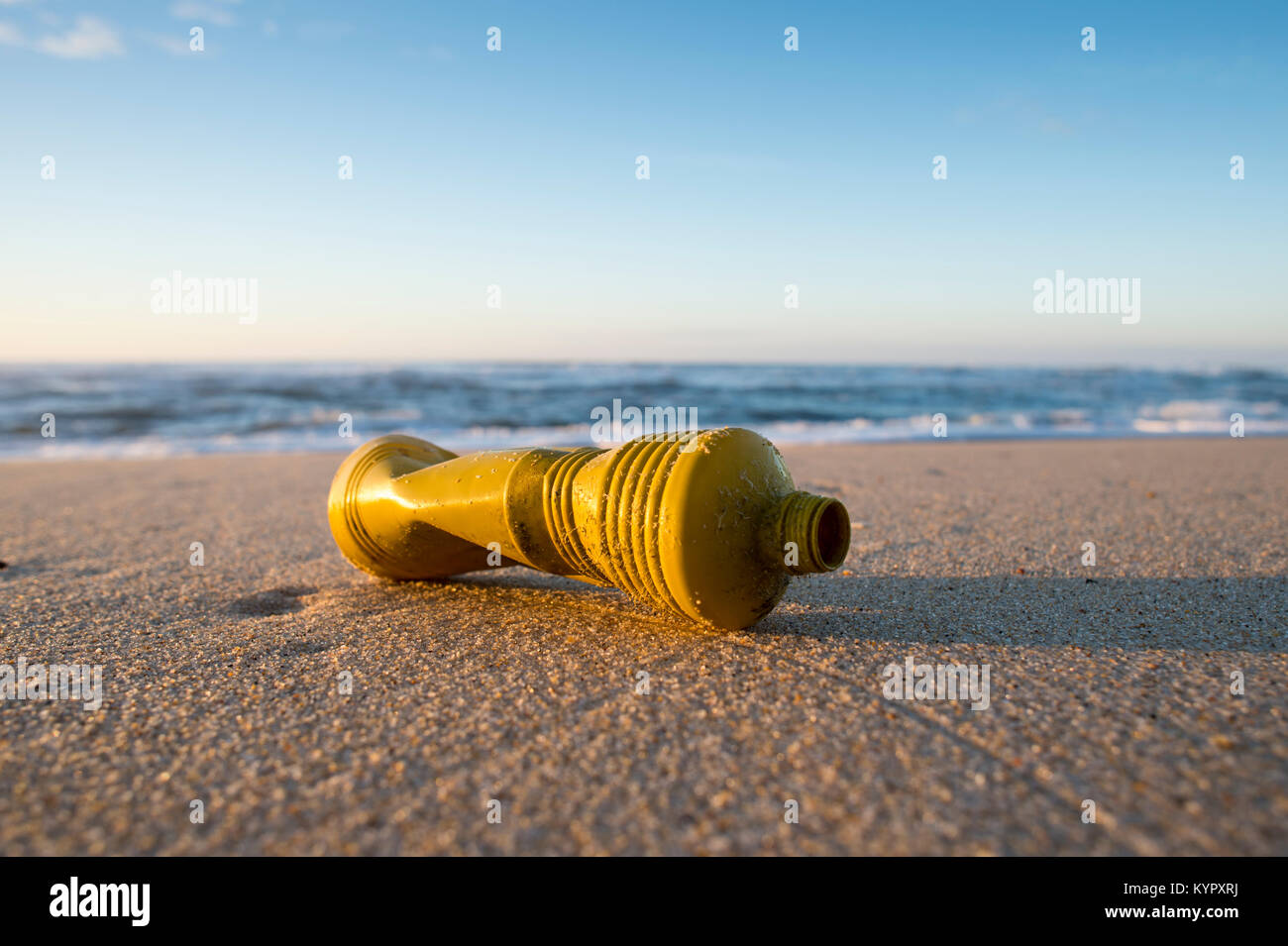 yellow plastic bottle washed up on a deserted beach, Ocean pollution with non-recyclable plastic. - Stock Image