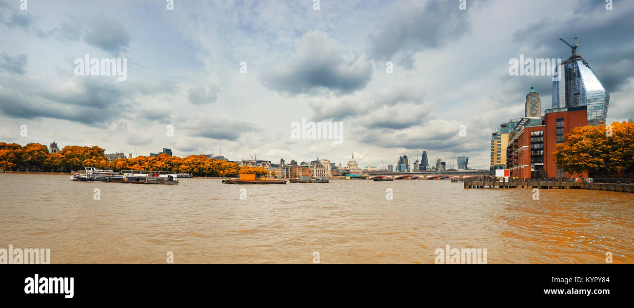 London, panoramic view over Thames river from Waterloo bridge on a gloomy overcast day in Fall. This image is toned. - Stock Image
