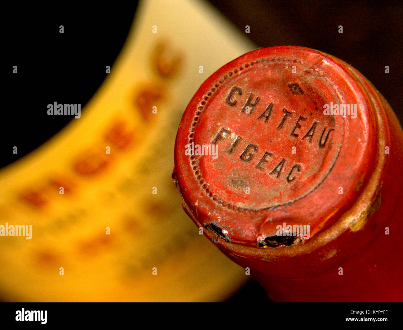 Foil capsule encapsulated bottle top 1970's Chateau Figeac in poor damaged condition, allowing possibility of 'corking' - Stock Image