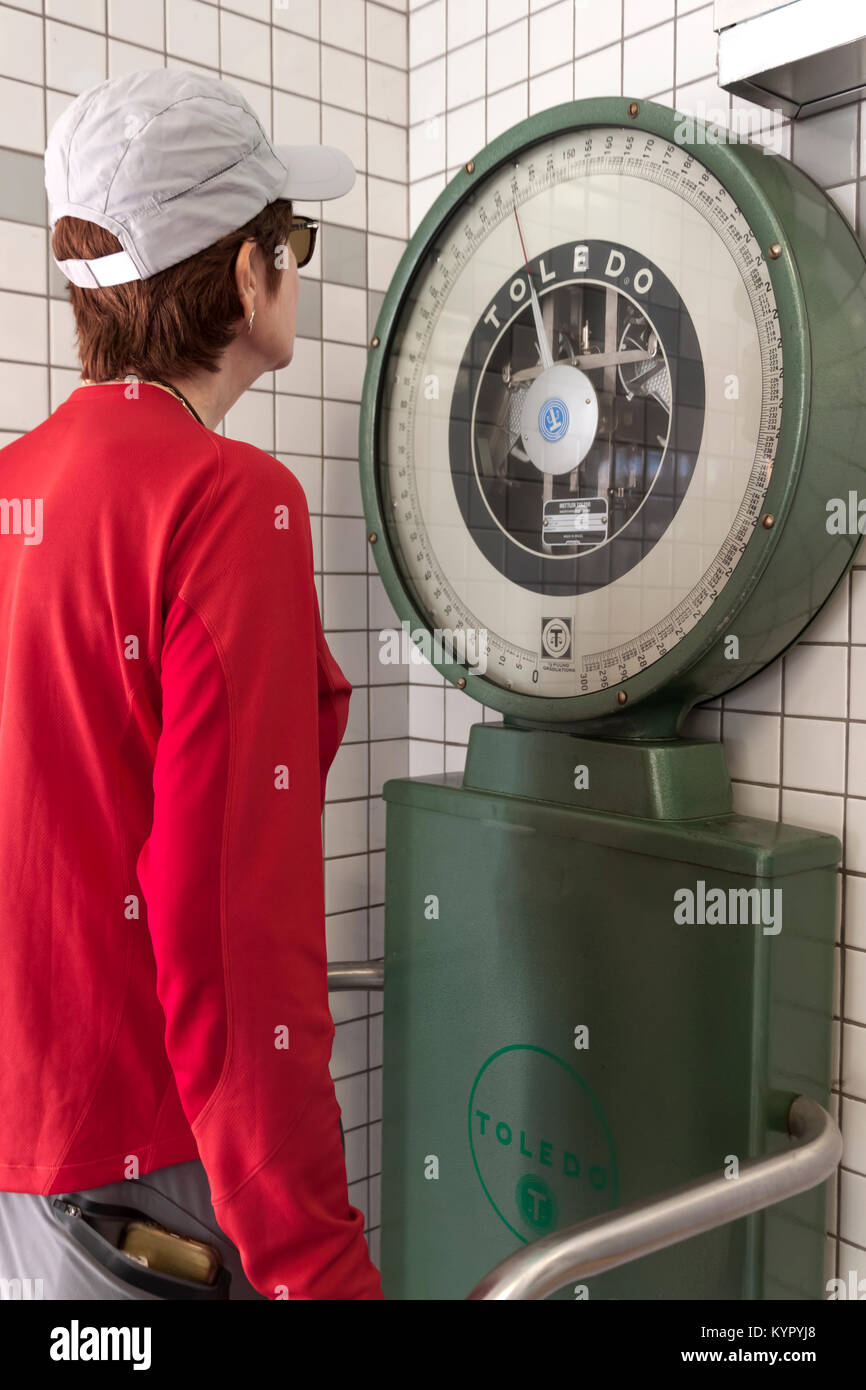Women standing and weighing herself on a large dial scale. - Stock Image