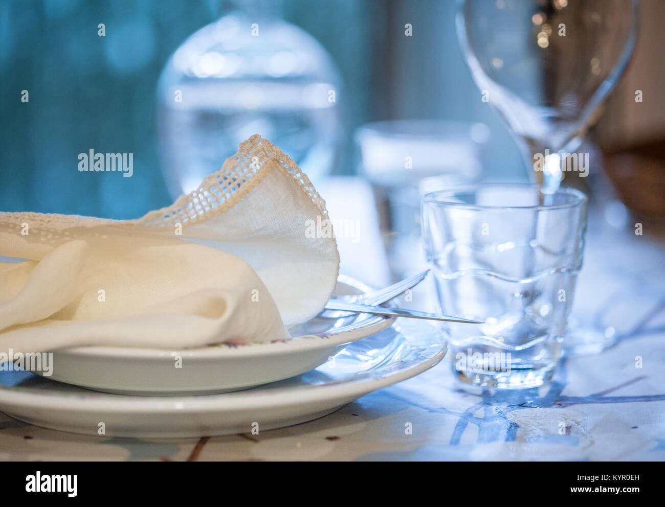 Elegant table set for dinning in a summer with white porcelain dishes, white vintage lace napkin and glassware - Stock Image