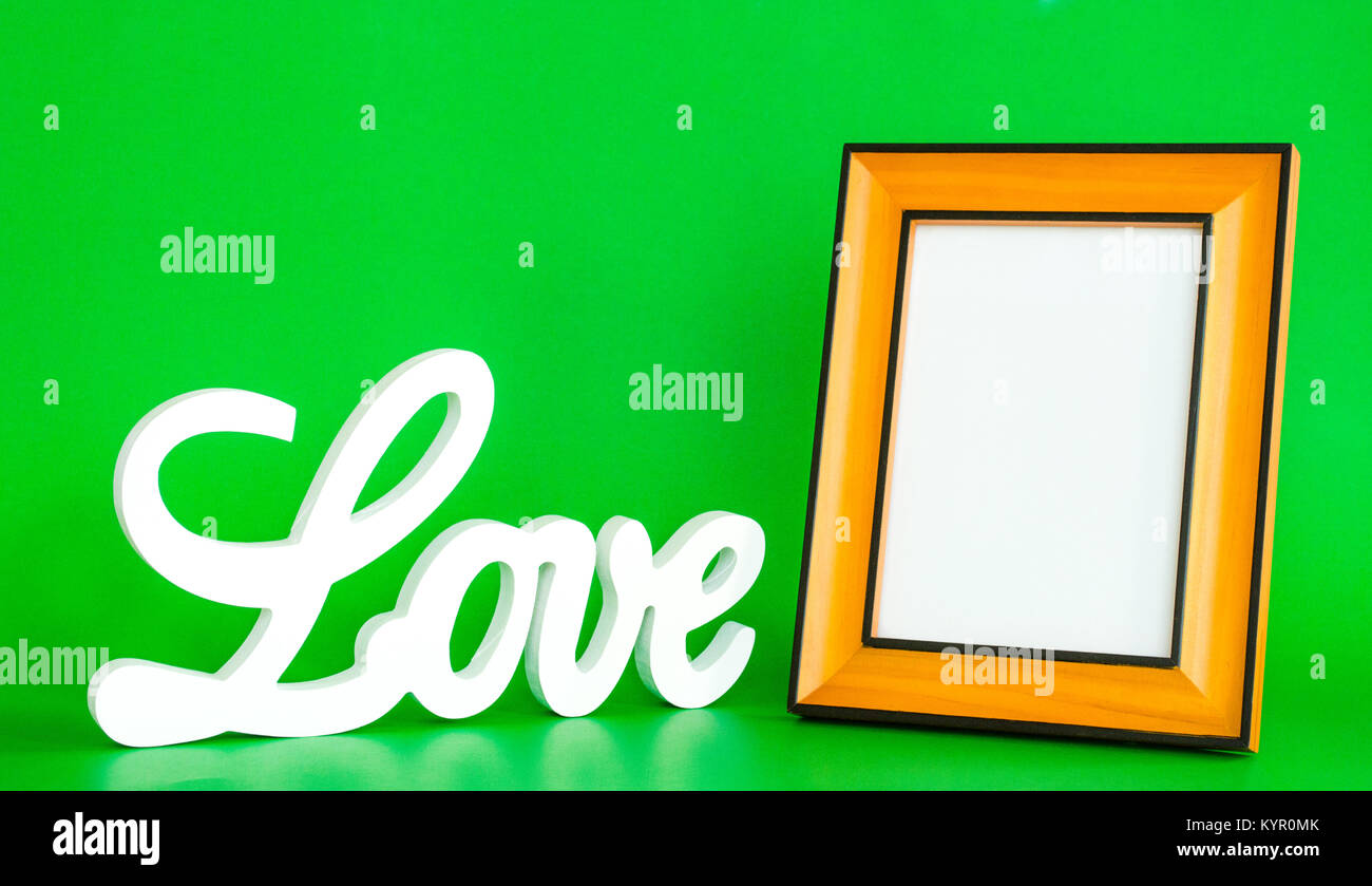 white love sign in cursive letters with an empty picture frame to customize on a green background