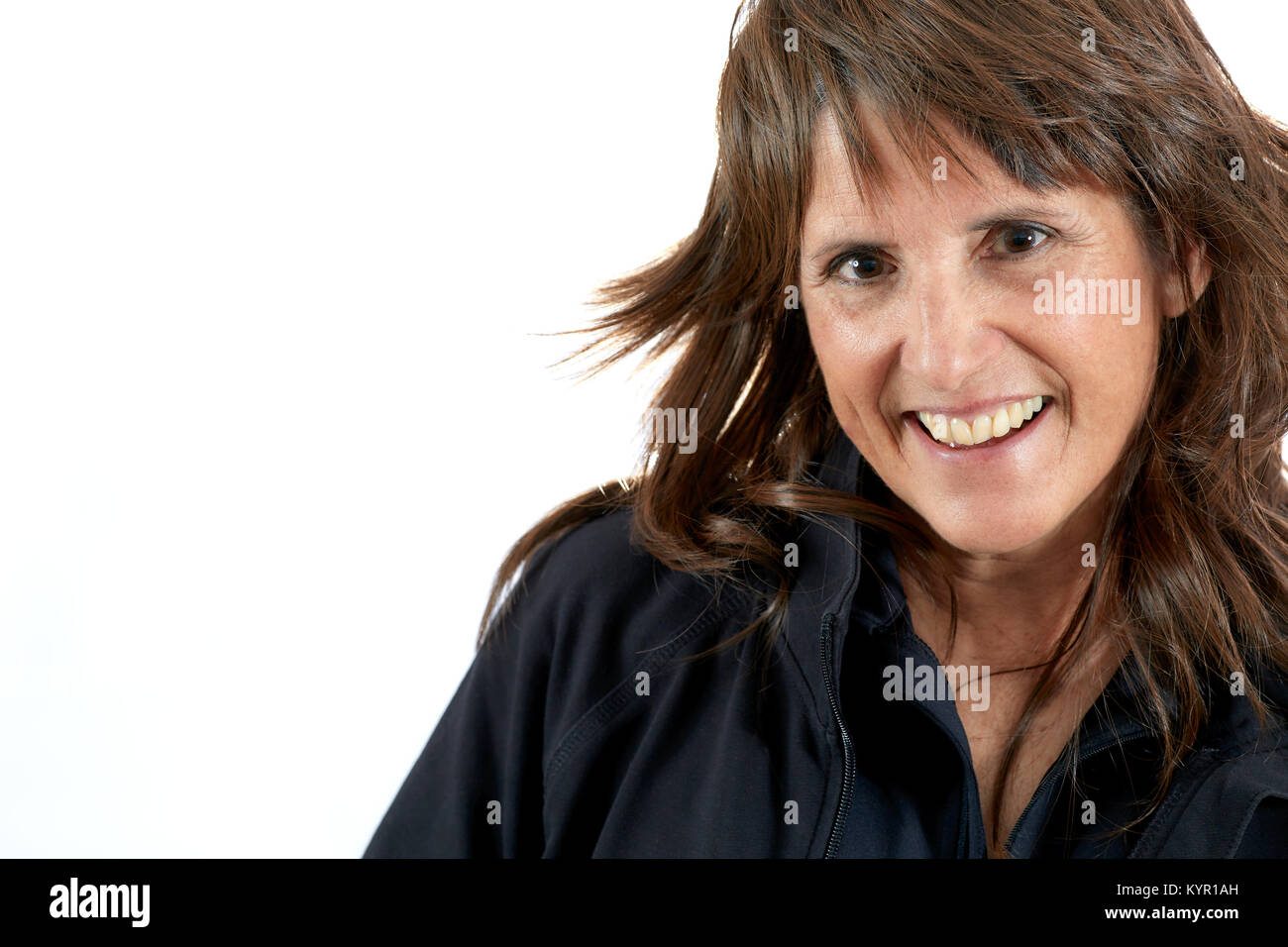 Attractive Middle aged woman with brown layered hair smiling isolated on white - Stock Image