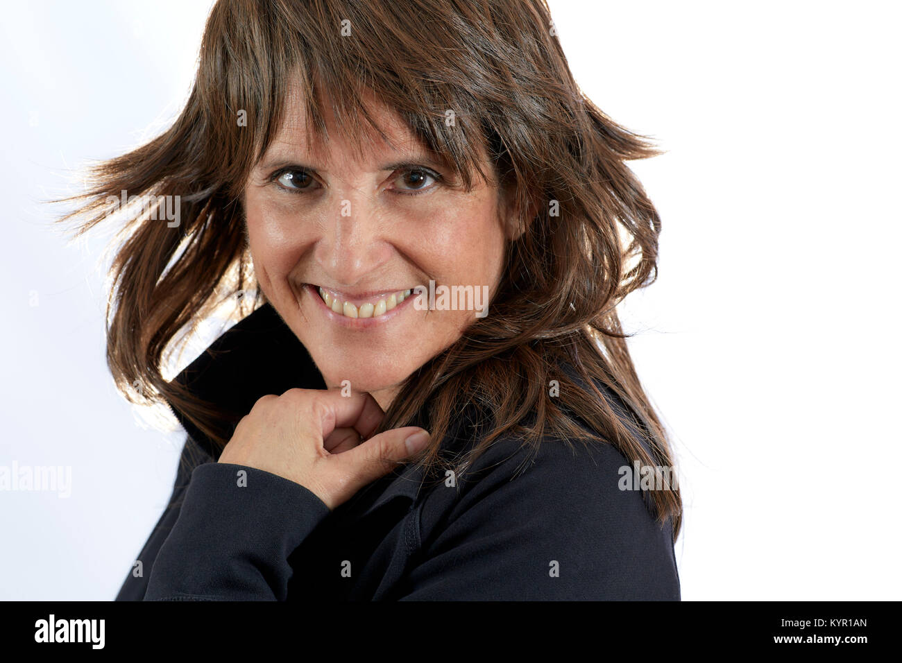 Middle aged woman with brown layered hair smiling isolated on white - Stock Image