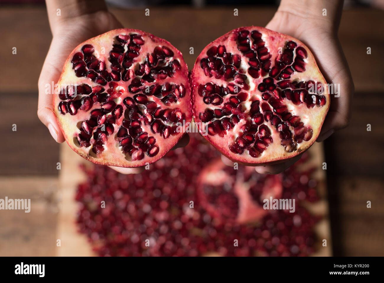 Hand Showing A Cut Pomegranate Fruit On Pomegranate Seeds