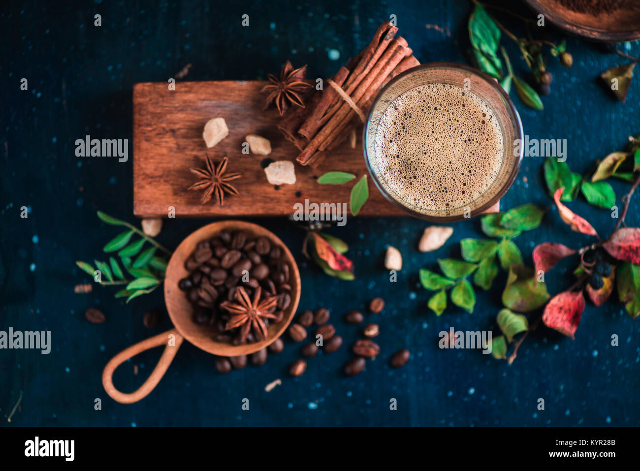 Flat lay with espresso shot with foam on a wooden box, coffee beans, arabica leaves, cinnamon and spices on dark - Stock Image