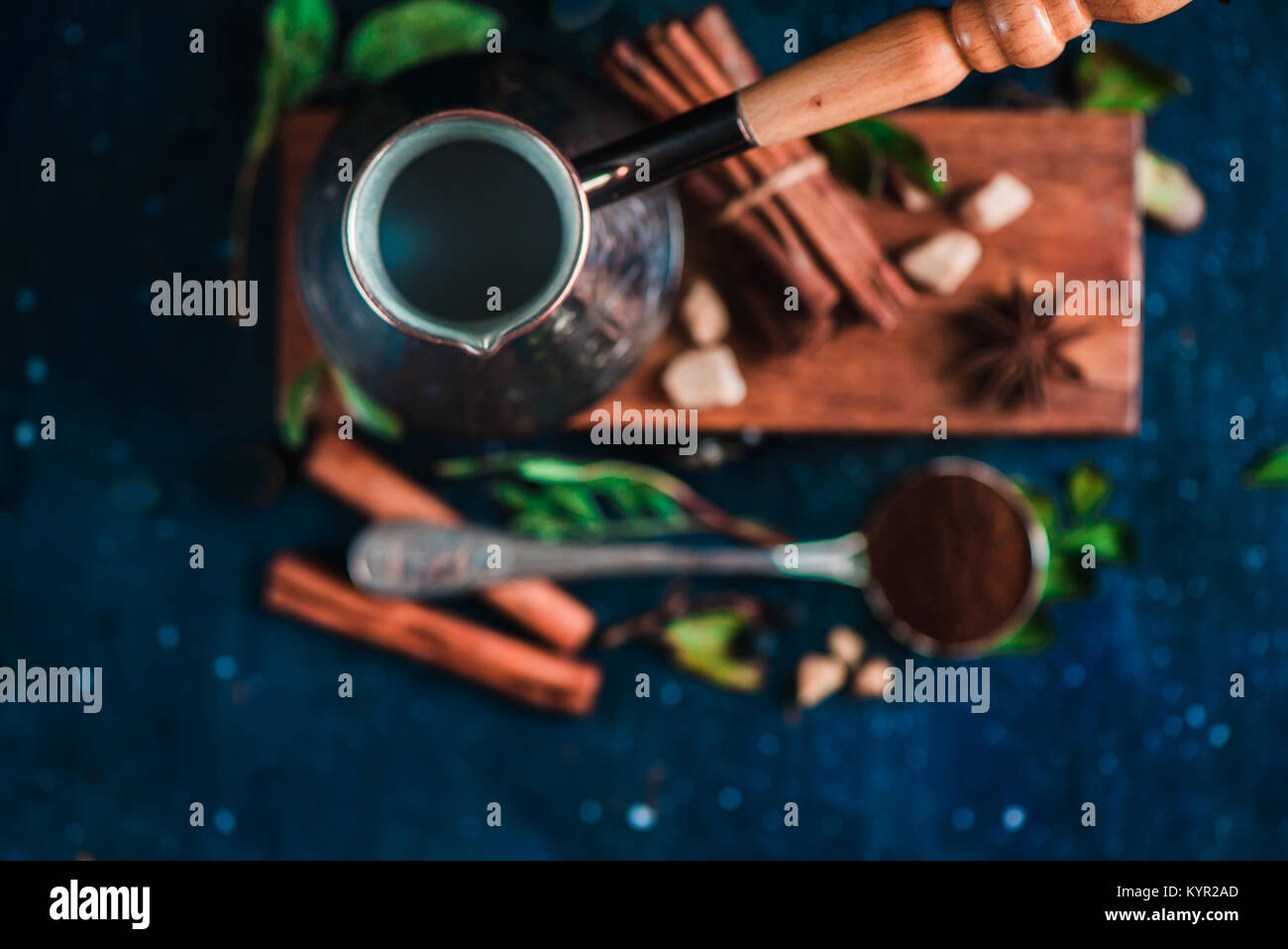 Flat lay with cezve, beans, cinnamon and spoon of ground coffee on a wooden background. Brewing coffee concept with - Stock Image