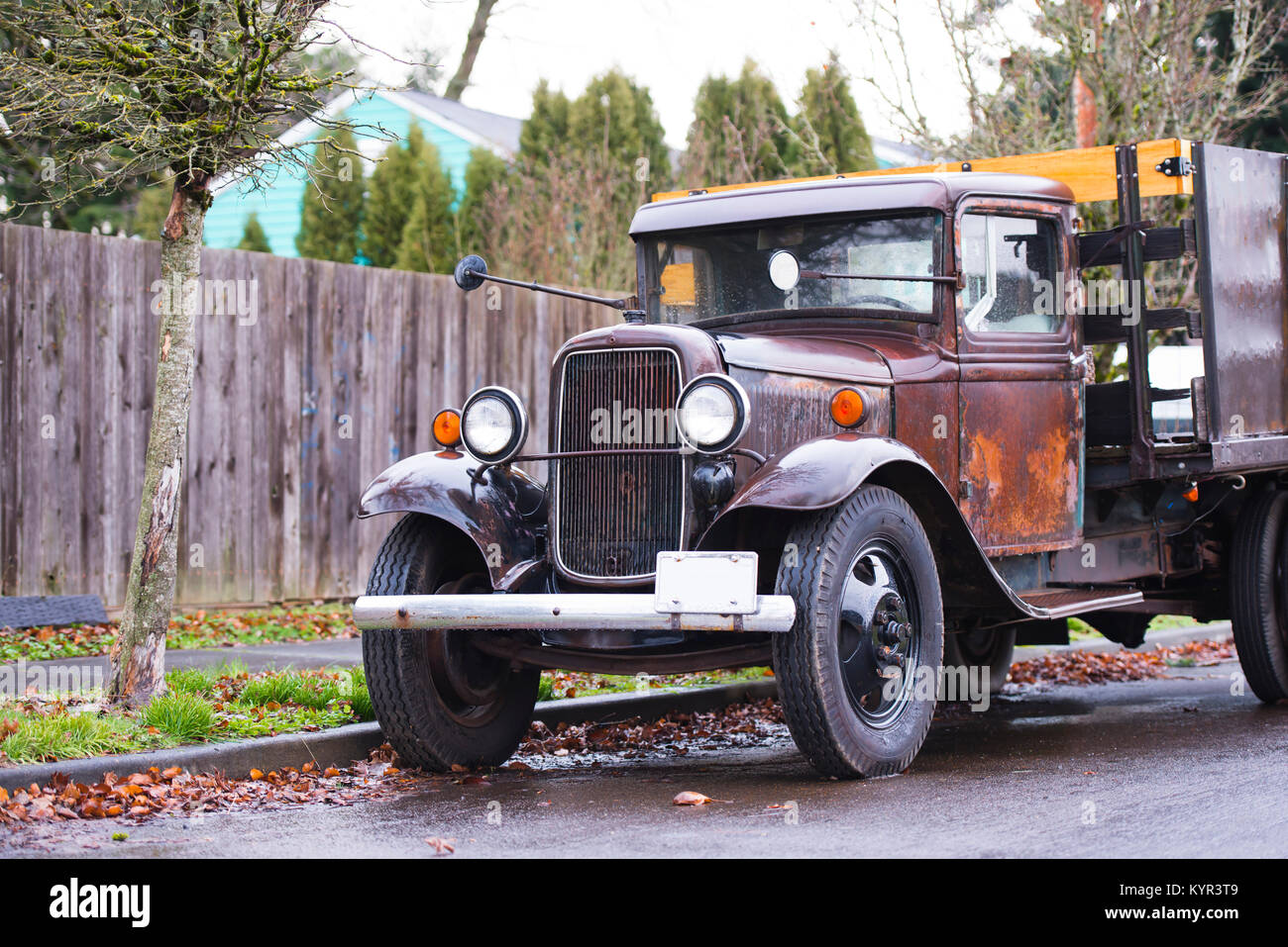 An old rarity rusty truck in working condition with a vintage design stands on the street under a fence in rainy - Stock Image