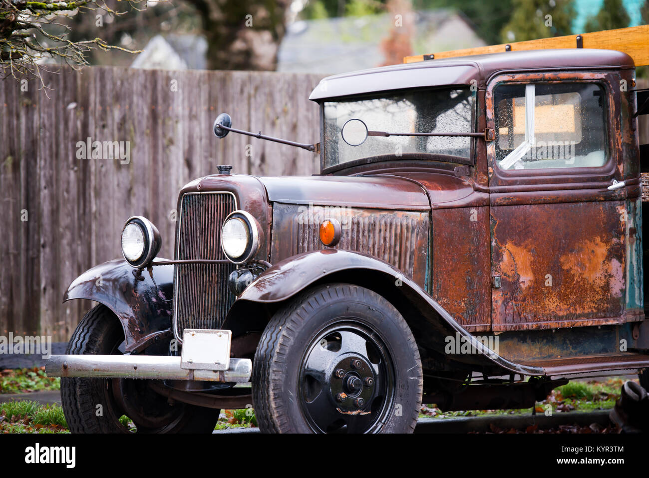 An old rarity rusty truck in working condition with a vintage design stands on the street under a fence in rainy Stock Photo