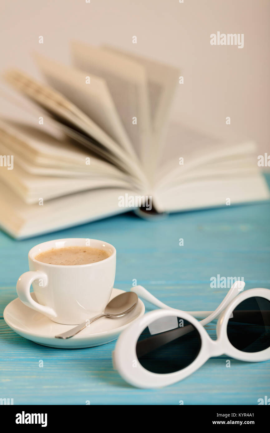 Book, sunglasses and cup of coffee on a wooden blue background. Selective focus. - Stock Image