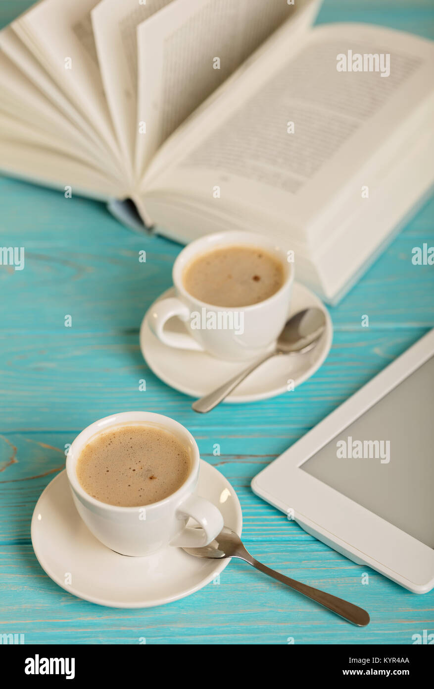 Book, e-book and two white cups of coffee on a wooden blue background. Selective focus. - Stock Image