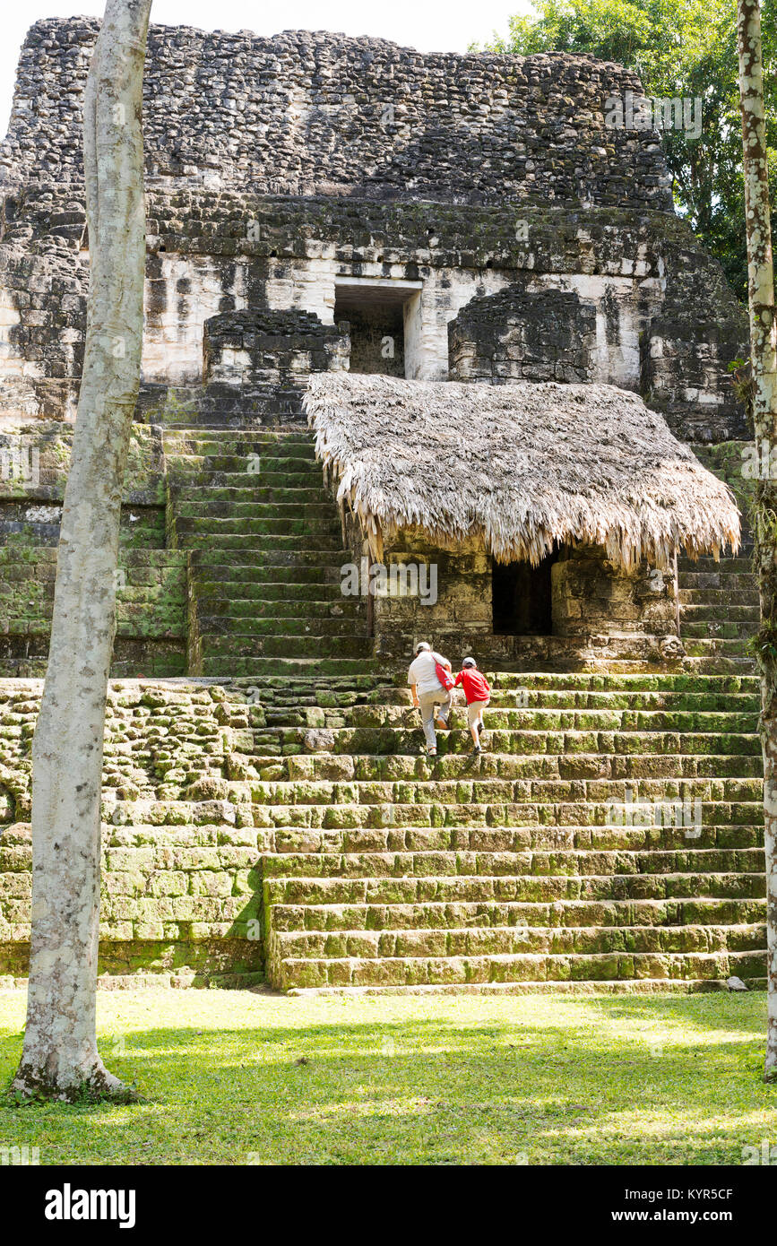 TIKAL, GUATEMALA - NOVEMBER 26: Unidentified people climbed mayan temple ruins at an archealogical site in Tikal - Stock Image