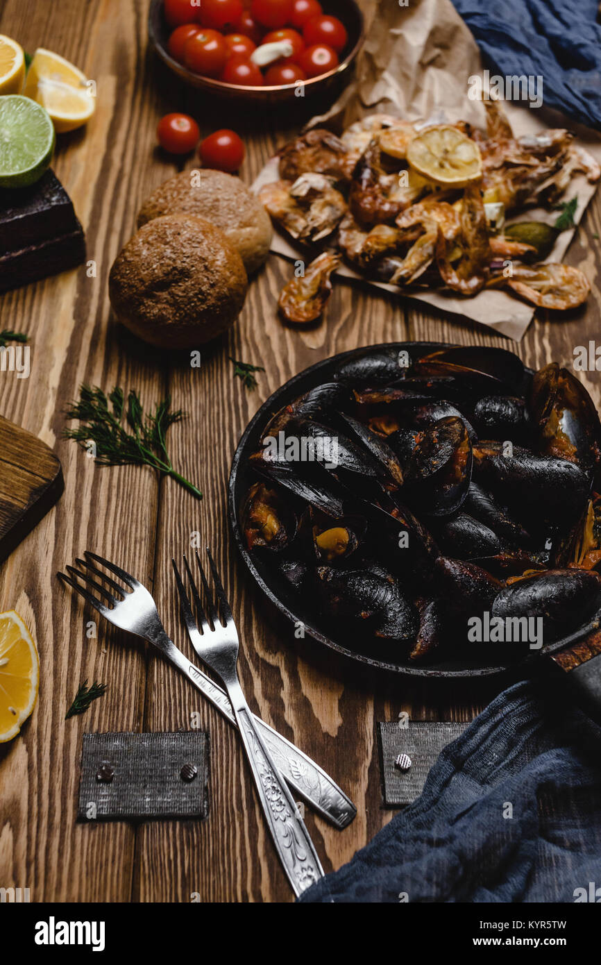 Assorted cooked seafood with bread and tomatoes on wooden table - Stock Image