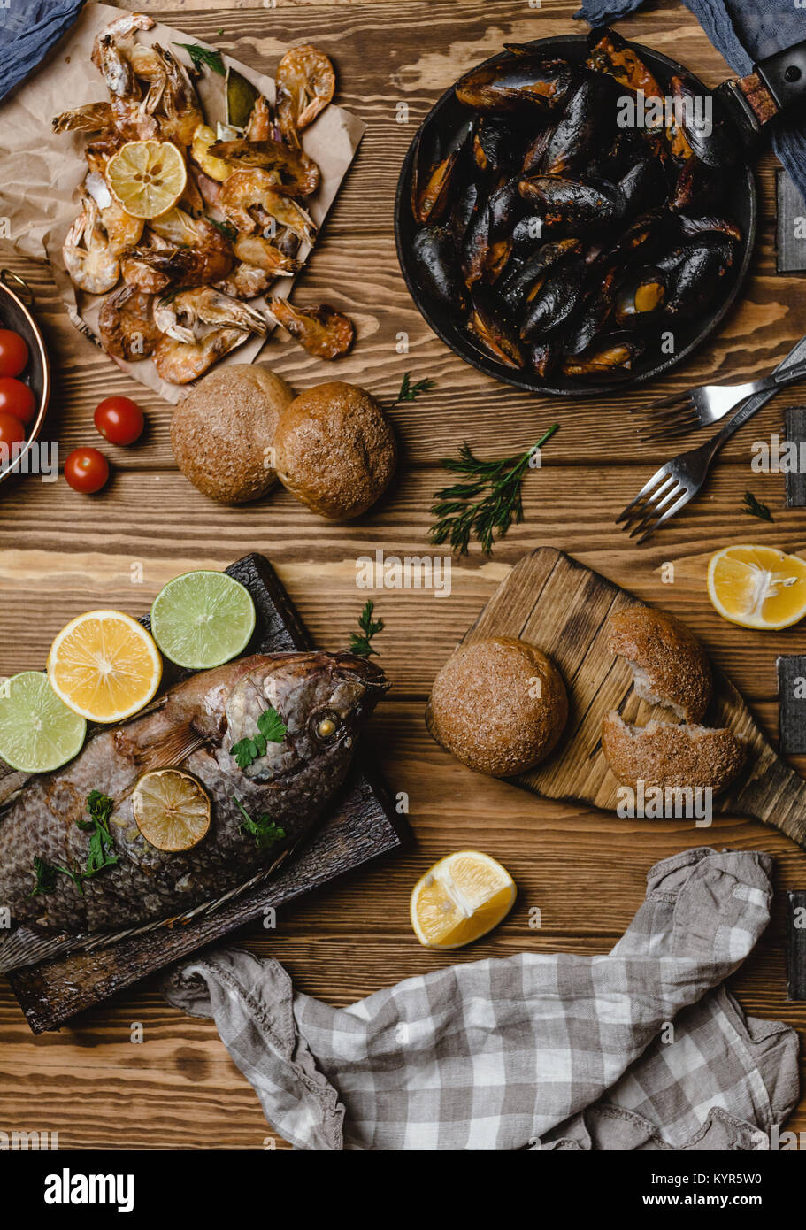 Top view of assorted seafood and baked fish with bread and tomatoes on wooden table - Stock Image