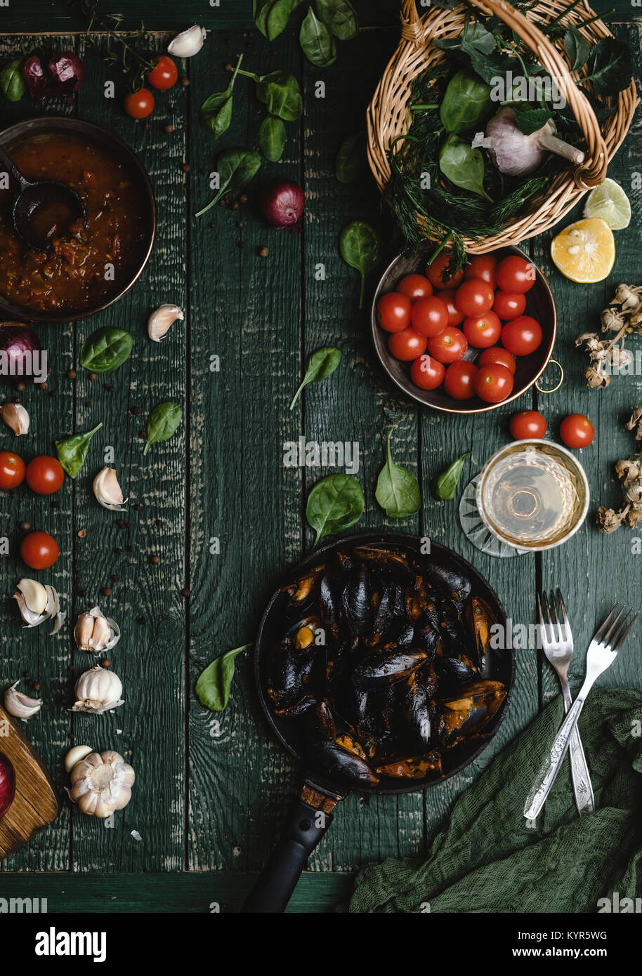 Top view of cooked mussels with shells served in pan with tomatoes, herbs and wine on wooden table - Stock Image