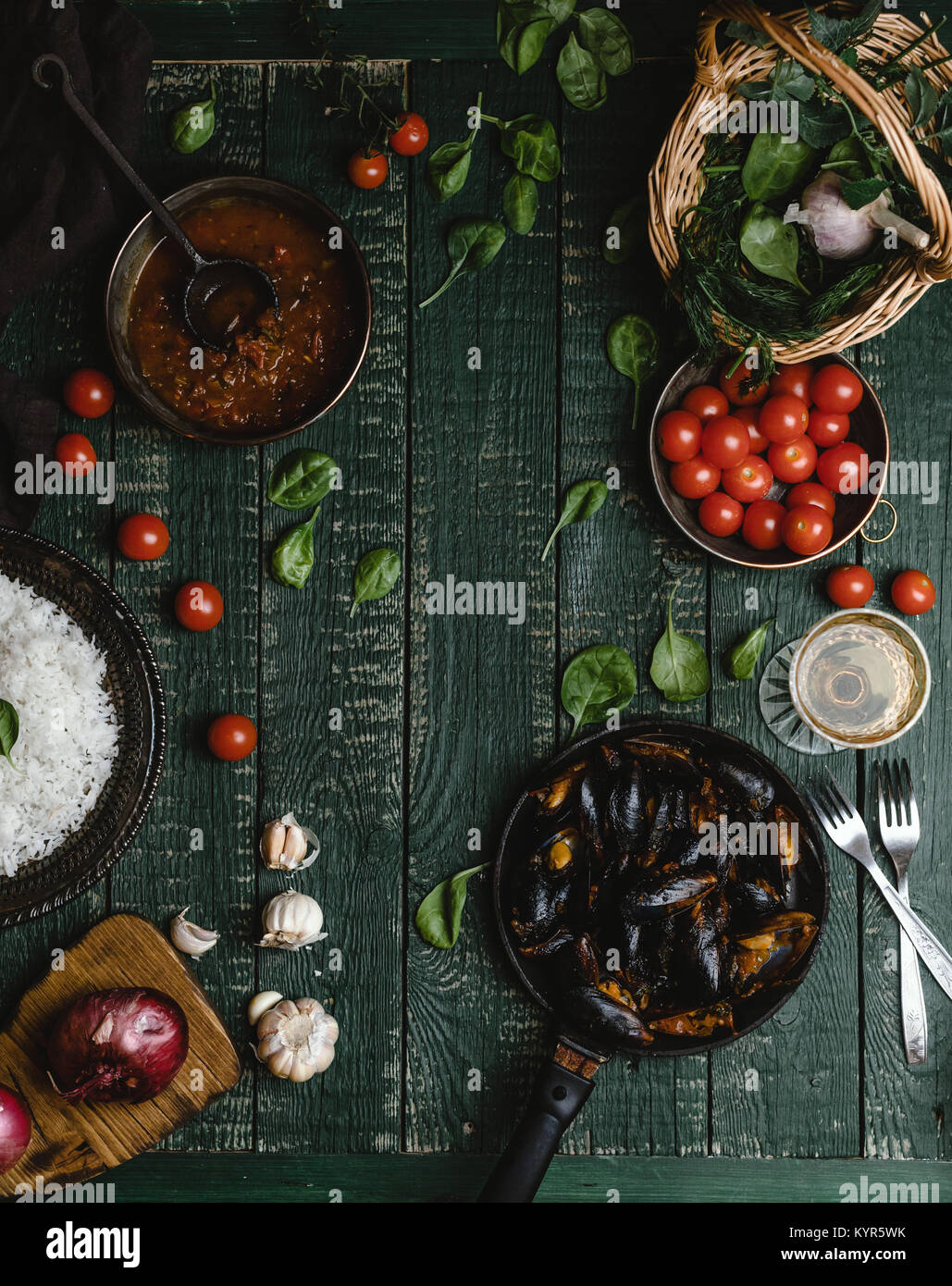 Top view of cooked mussels with shells served in pan with tomatoes, herbs and wine on rustic table - Stock Image