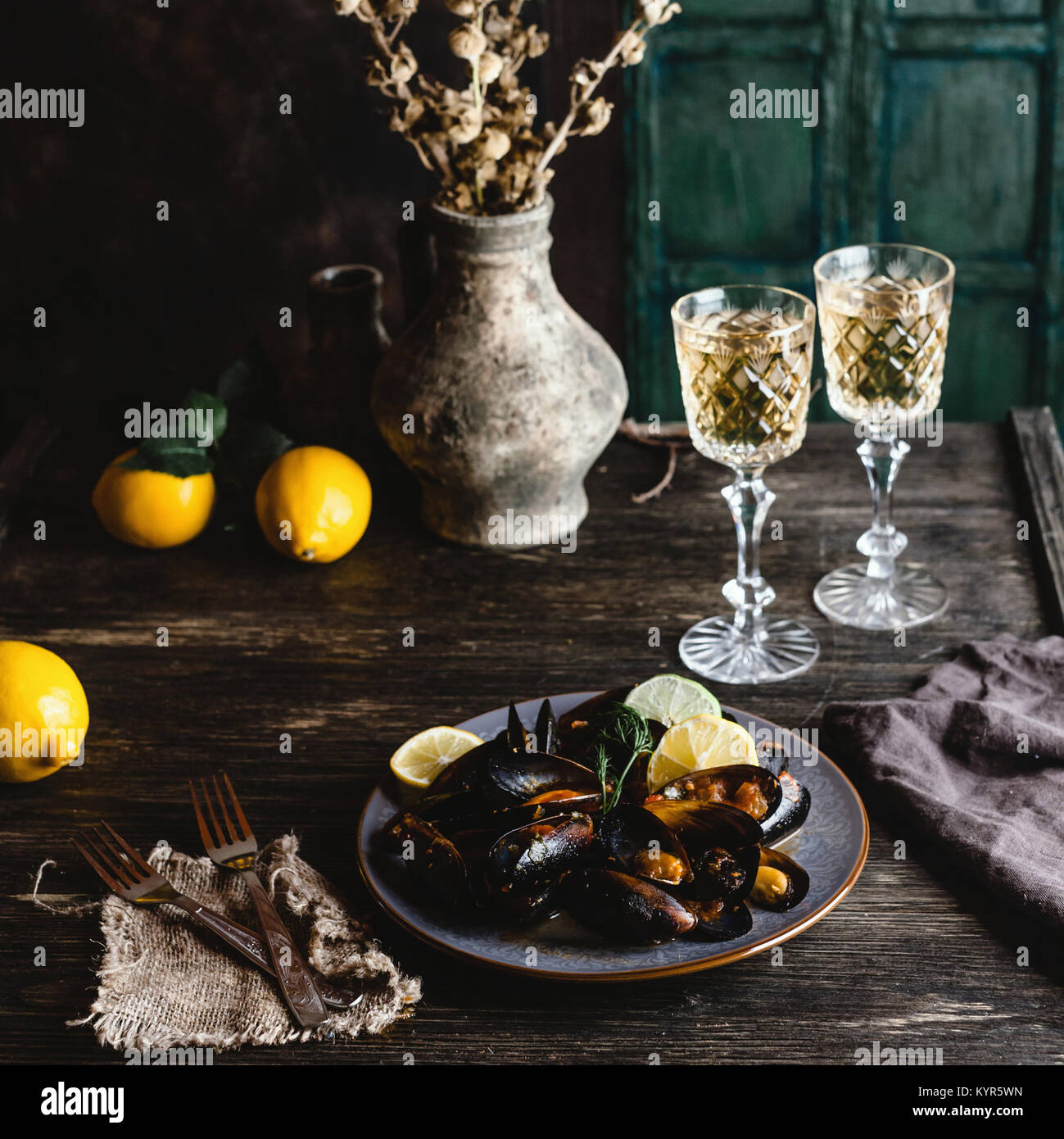 Cooked mussels with shells served on plate with two glasses of white wine on wooden table - Stock Image