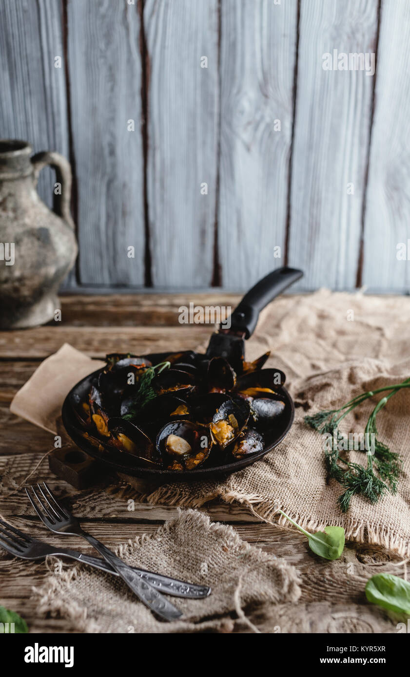 gourmet fried mussels with shells on frying pan and forks on table Stock Photo