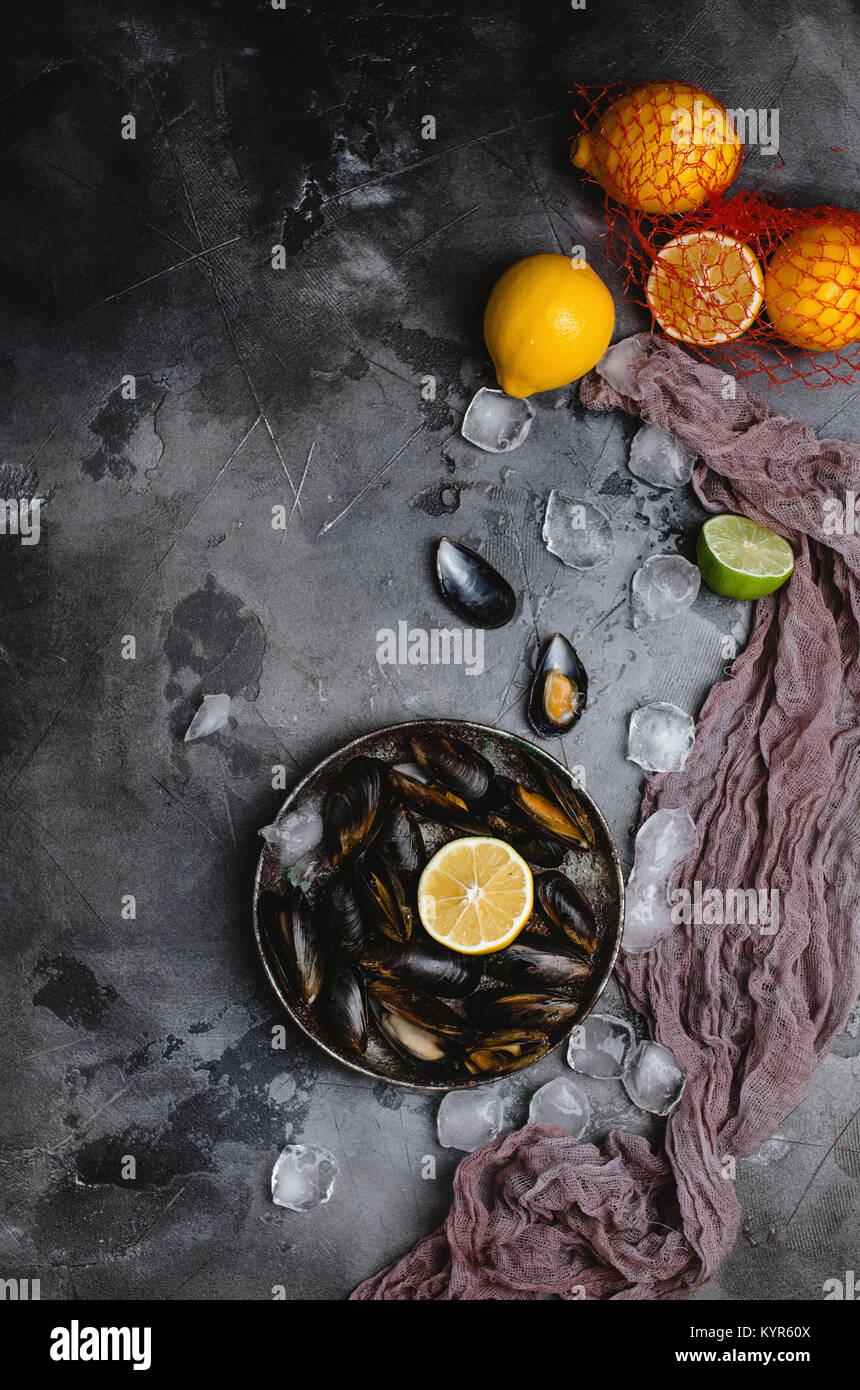 top view of delicious mussels with shells on vintage plate and citrus fruits with ice cubes on grey   - Stock Image
