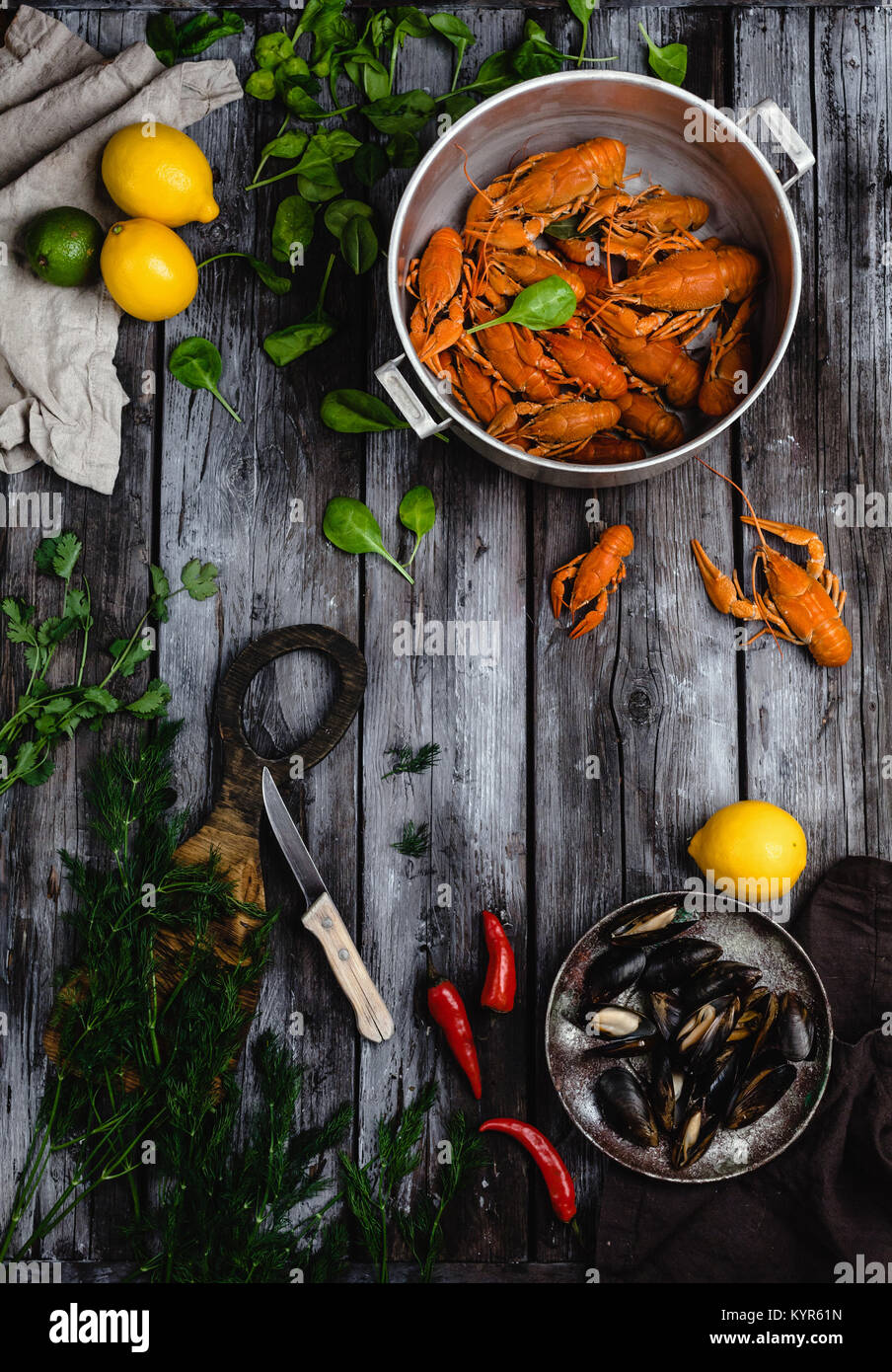 top view of lobsters and mussels in pans and citrus fruits with herbs on rustic wooden table - Stock Image