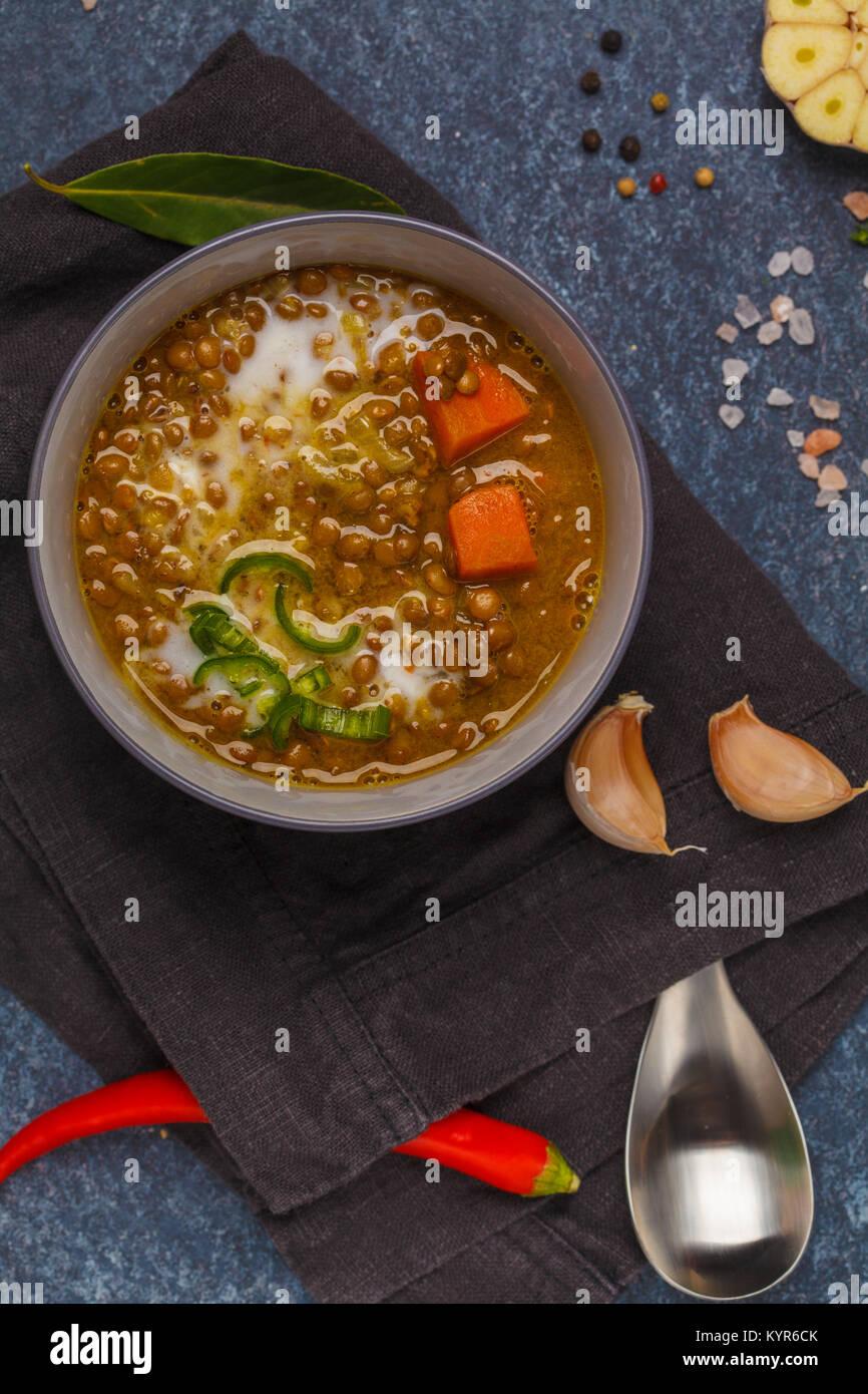 Indian vegetarian lentil soup, mung dal. Indian food spice concept. Dark background, top view. - Stock Image