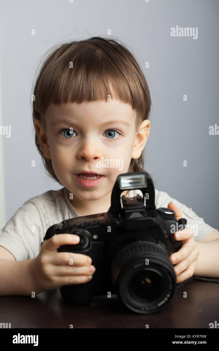 Beautiful child in with professional camera. Little boy with long blond hair photographing in the Studio - Stock Image