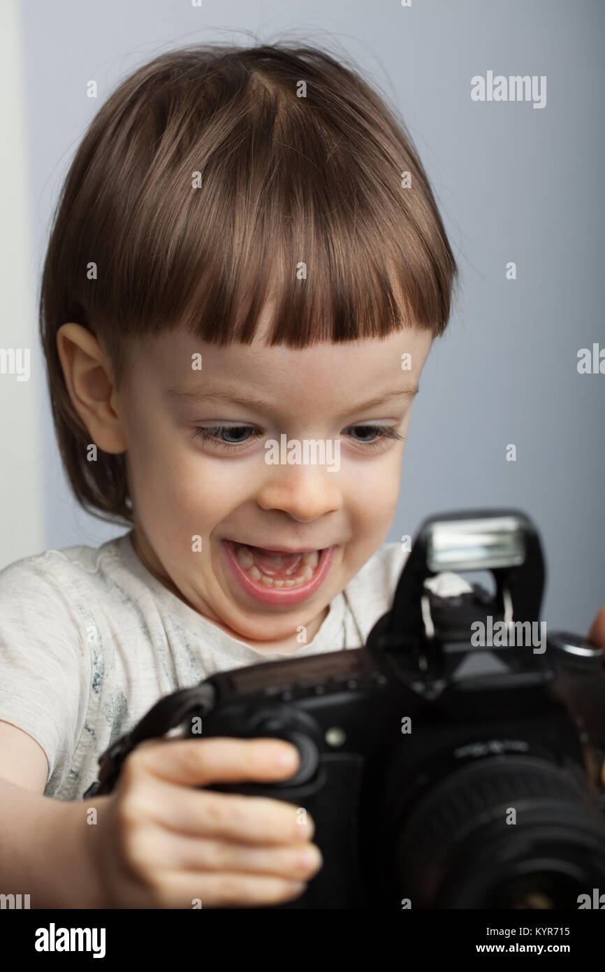 Beautiful child in with professional camera. Little boy with long blond hair photographing in the Studio. He looks - Stock Image