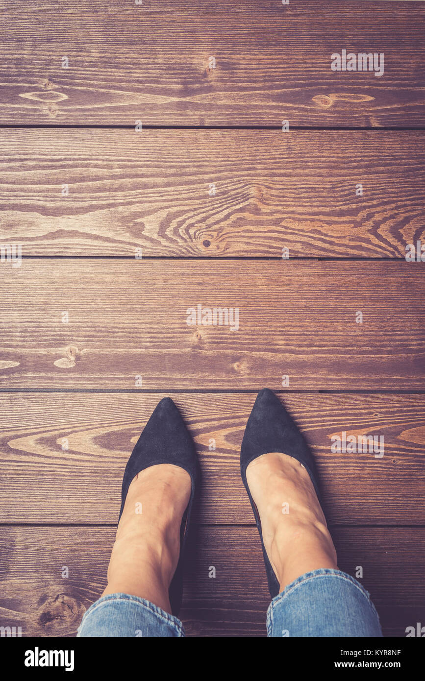 Woman in high heels standing on wooden floor - Stock Image