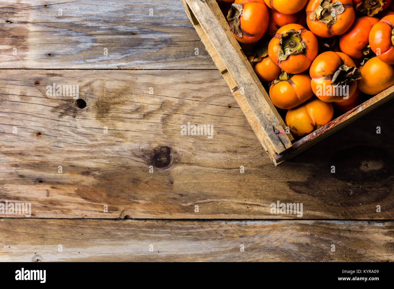 Box of fresh fruits persimmon kaki on old wooden background. Copy space - Stock Image