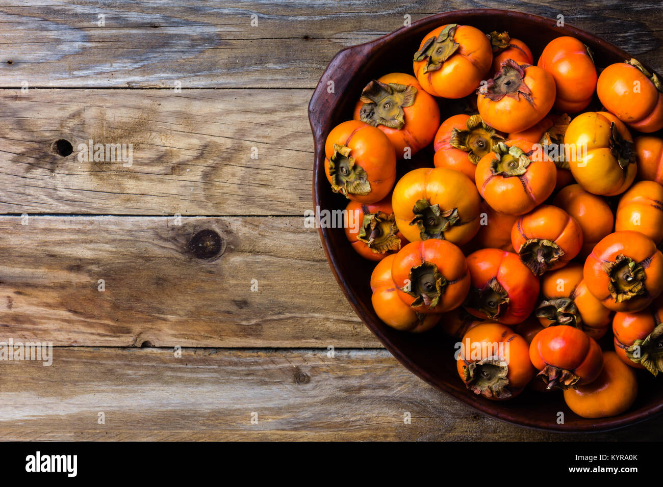 Pot of fresh fruits persimmon kaki on old wooden background. Copy space - Stock Image