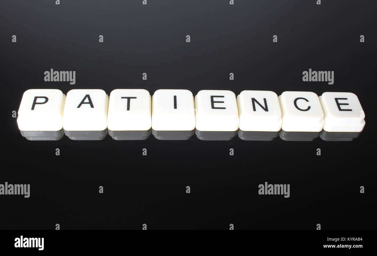 Patience text word title caption label cover backdrop background. Alphabet letter toy blocks on black reflective - Stock Image