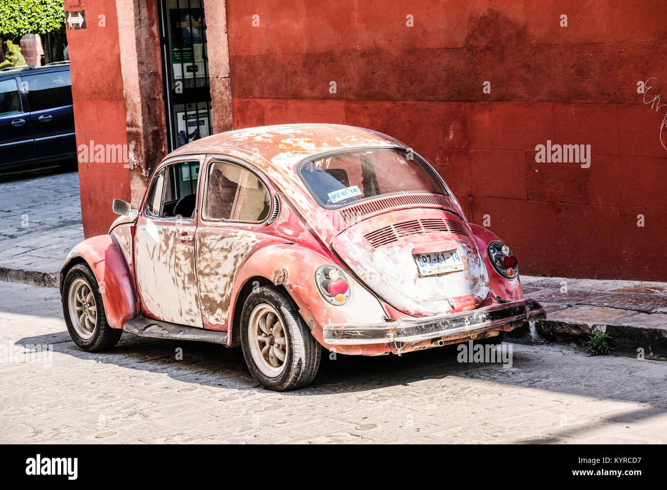 A very old adn beat up fade red colored Volkswagen Beetle parked at a street corner in San Miguel de Allende,Mexico - Stock Image