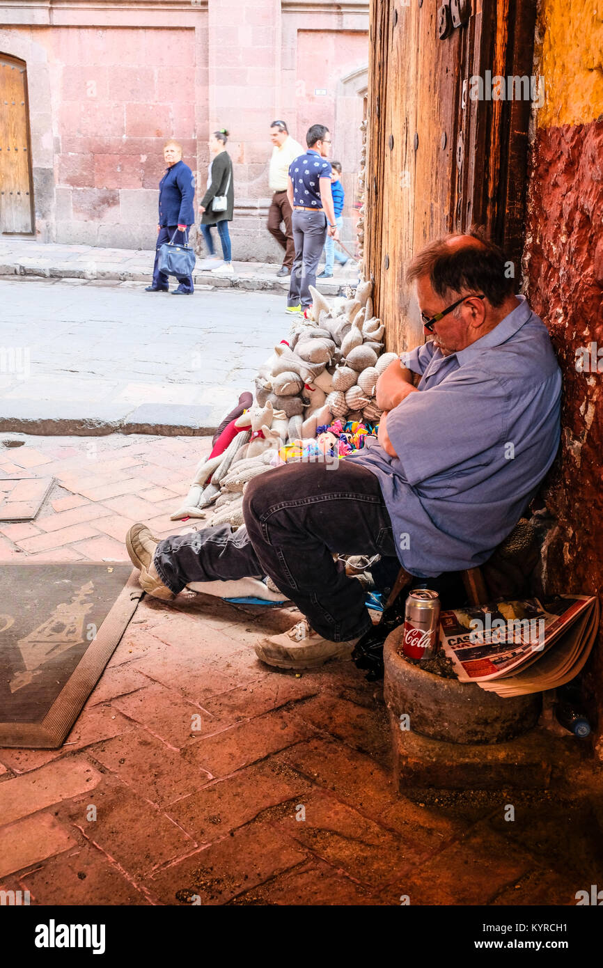 A stuffed toy vendor napping by a door in San Miguel de Allende,Mexico - Stock Image