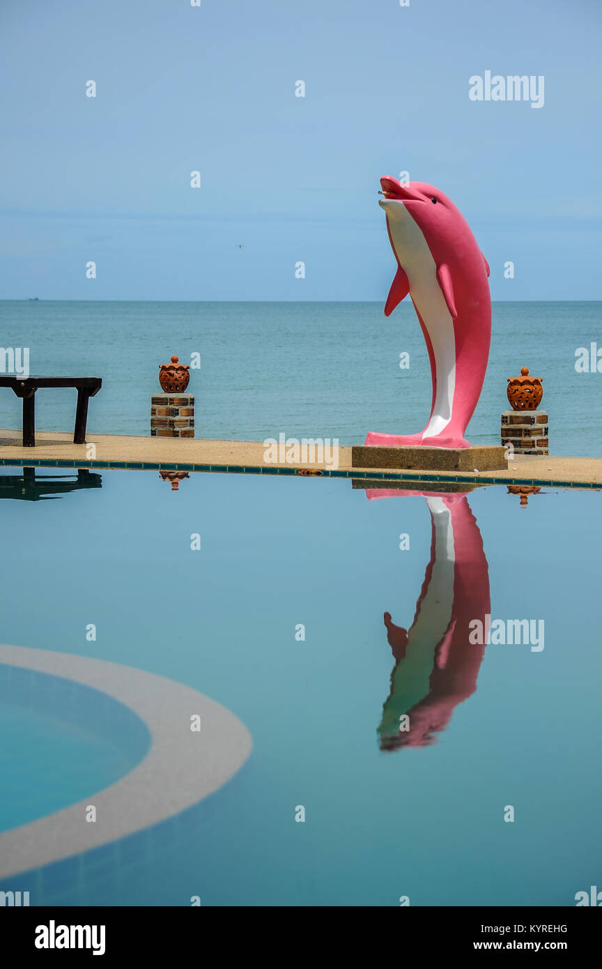 Pink dolphin statue beside swimming pool close to sea. - Stock Image