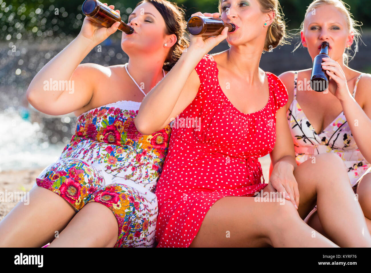 Friends drinking beer at river beach - Stock Image