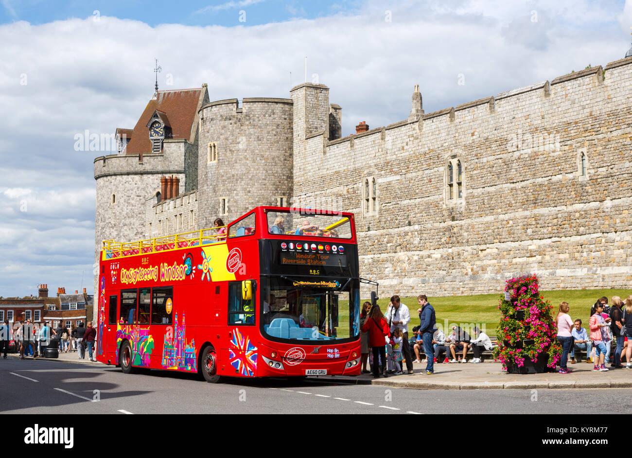 Open-top sightseeing red bus parked outside the walls and tower of Windsor Castle viewed from the town centre on - Stock Image