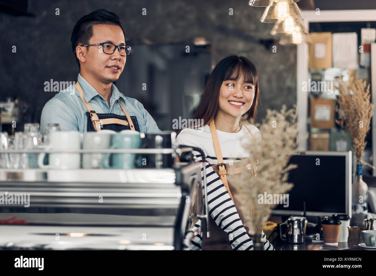 Asia Barista waiter smile and talking to customer in coffee shop,Two cafe owner at counter bar,Food and drink business - Stock Image