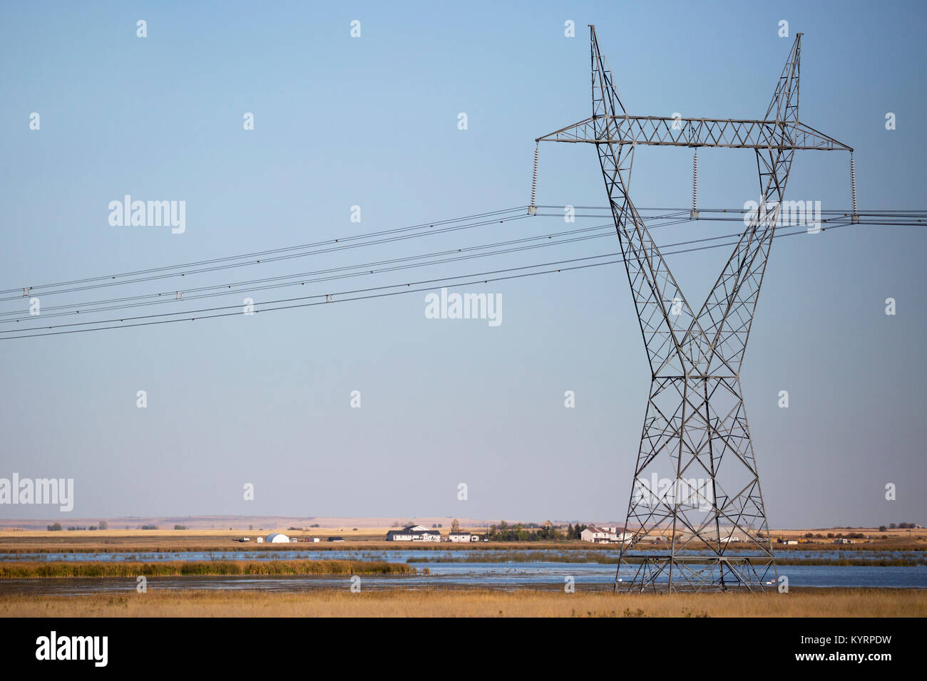 Transmission tower across prairie lake - Stock Image