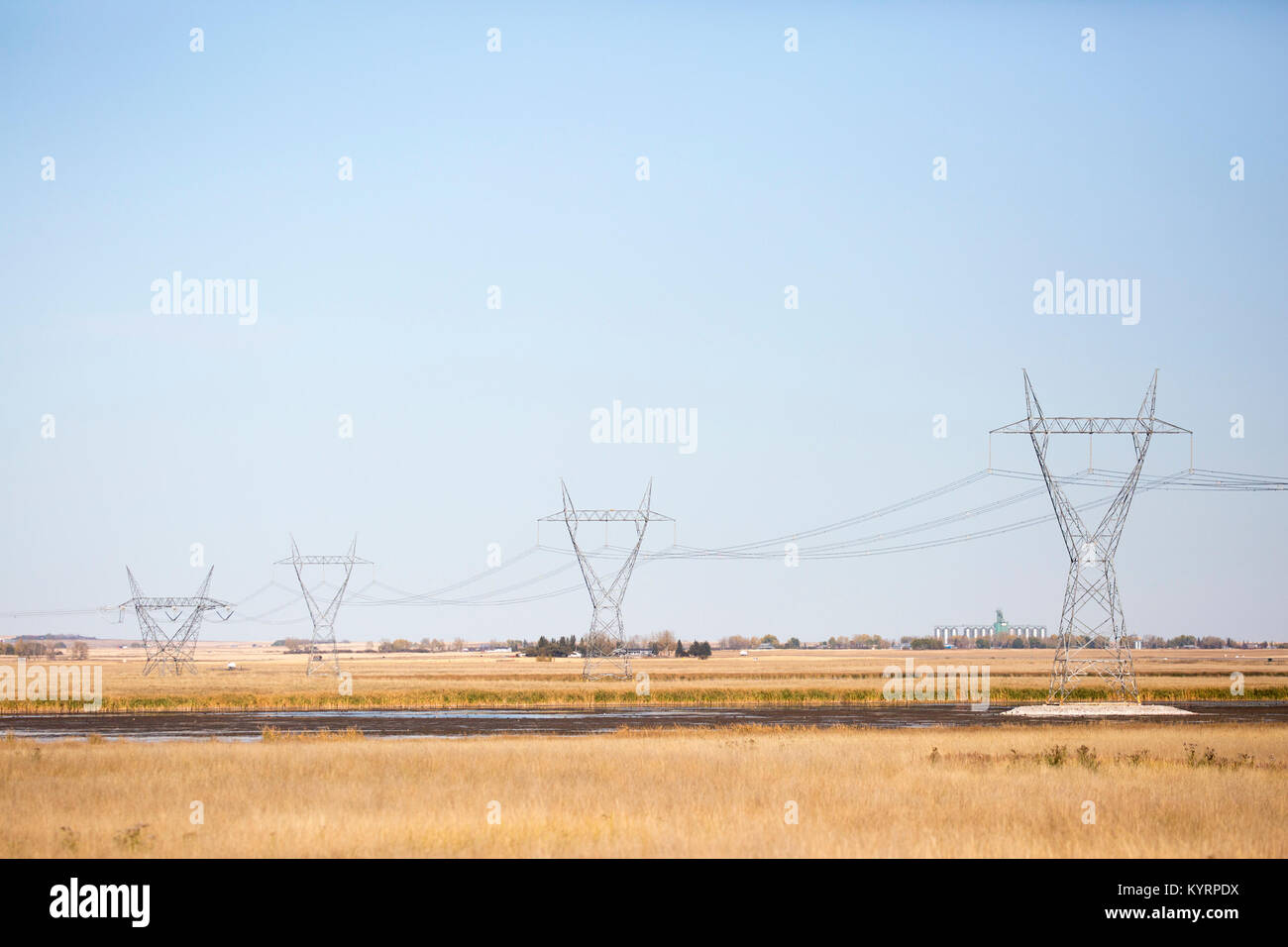 Transmission towers across prairie lake - Stock Image