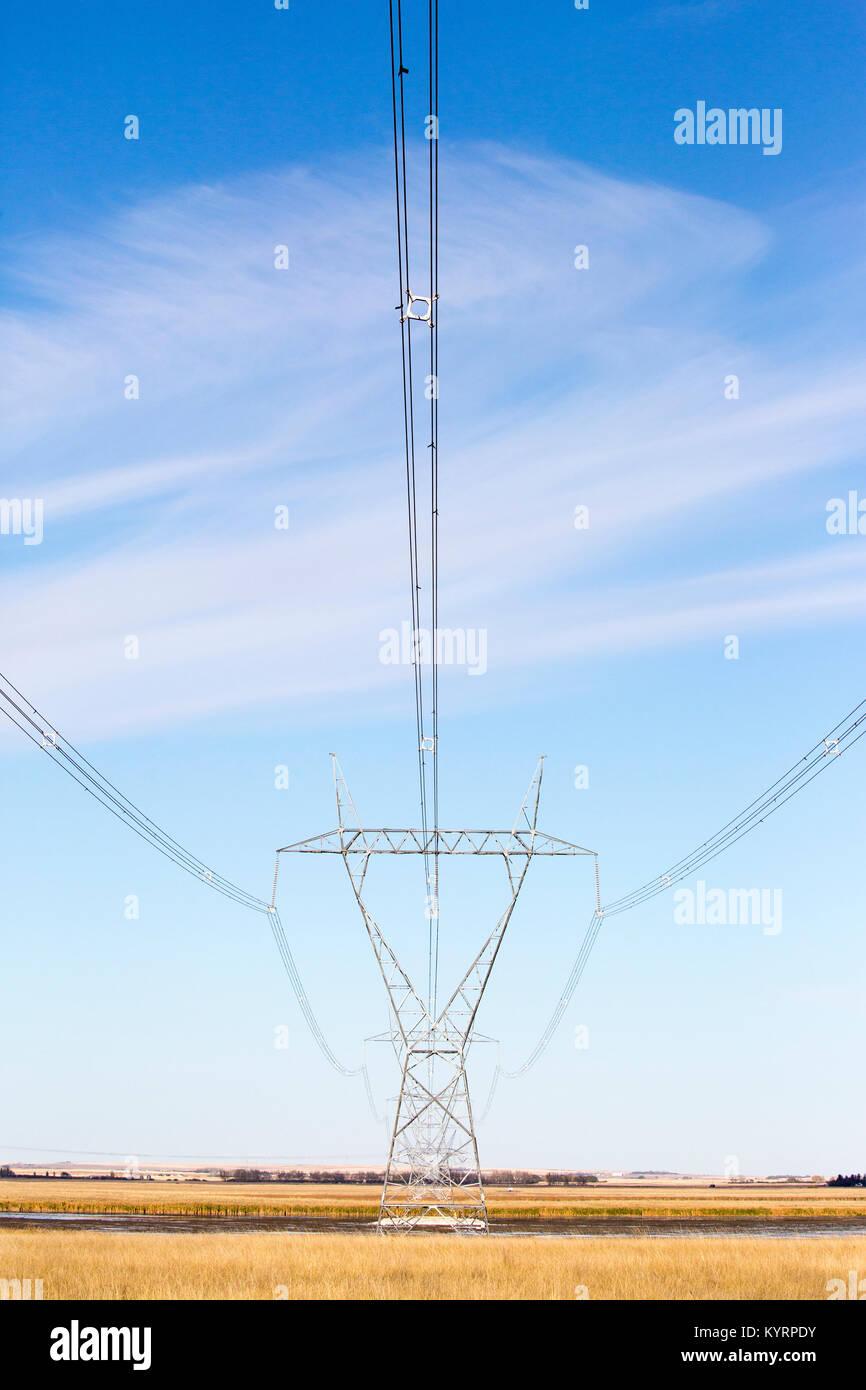 Transmission tower across prairie lake - Stock Image