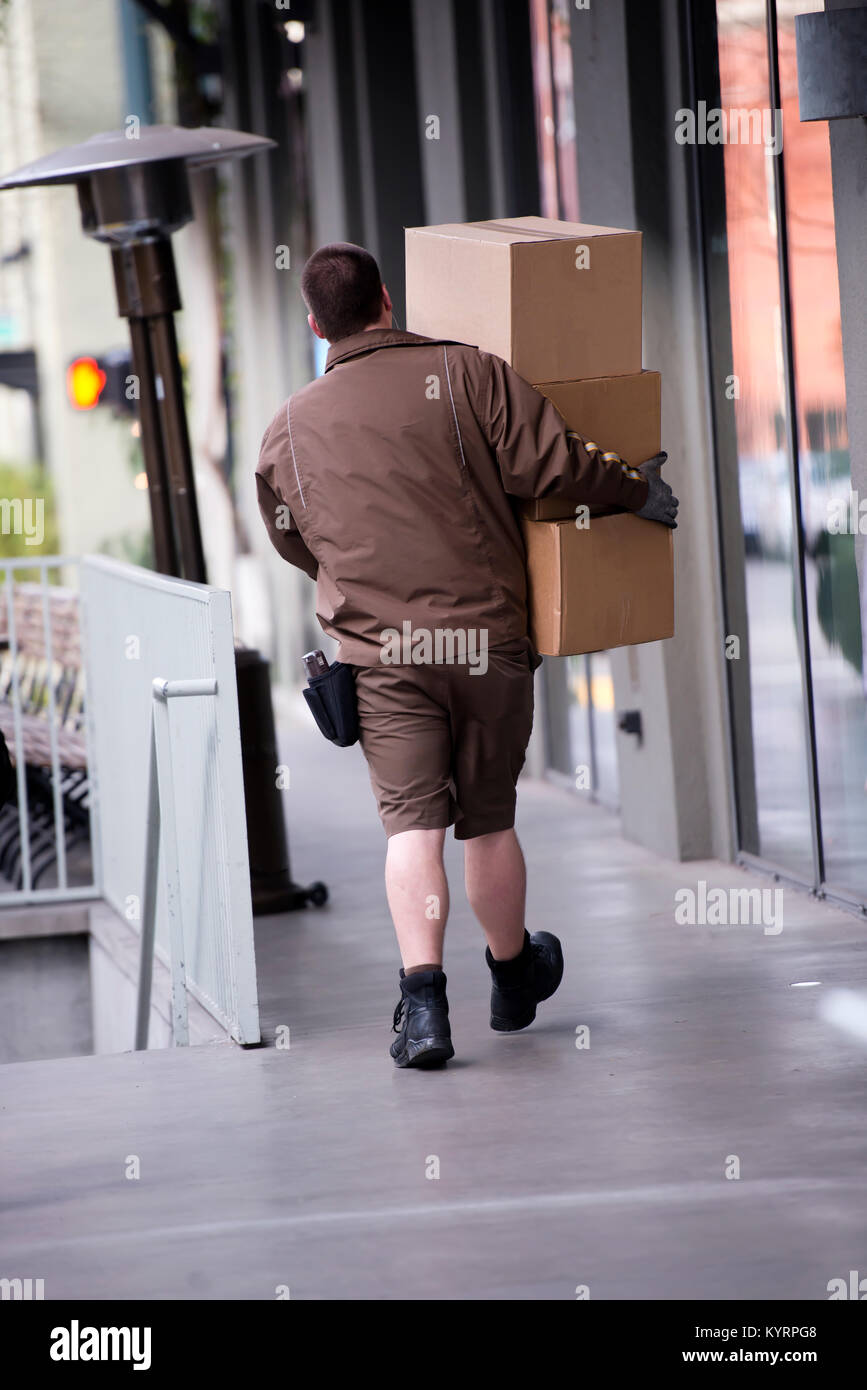 The deliverer of parcels in uniform with boxes in their hands delivers them to the addressee with a brisk step towards - Stock Image