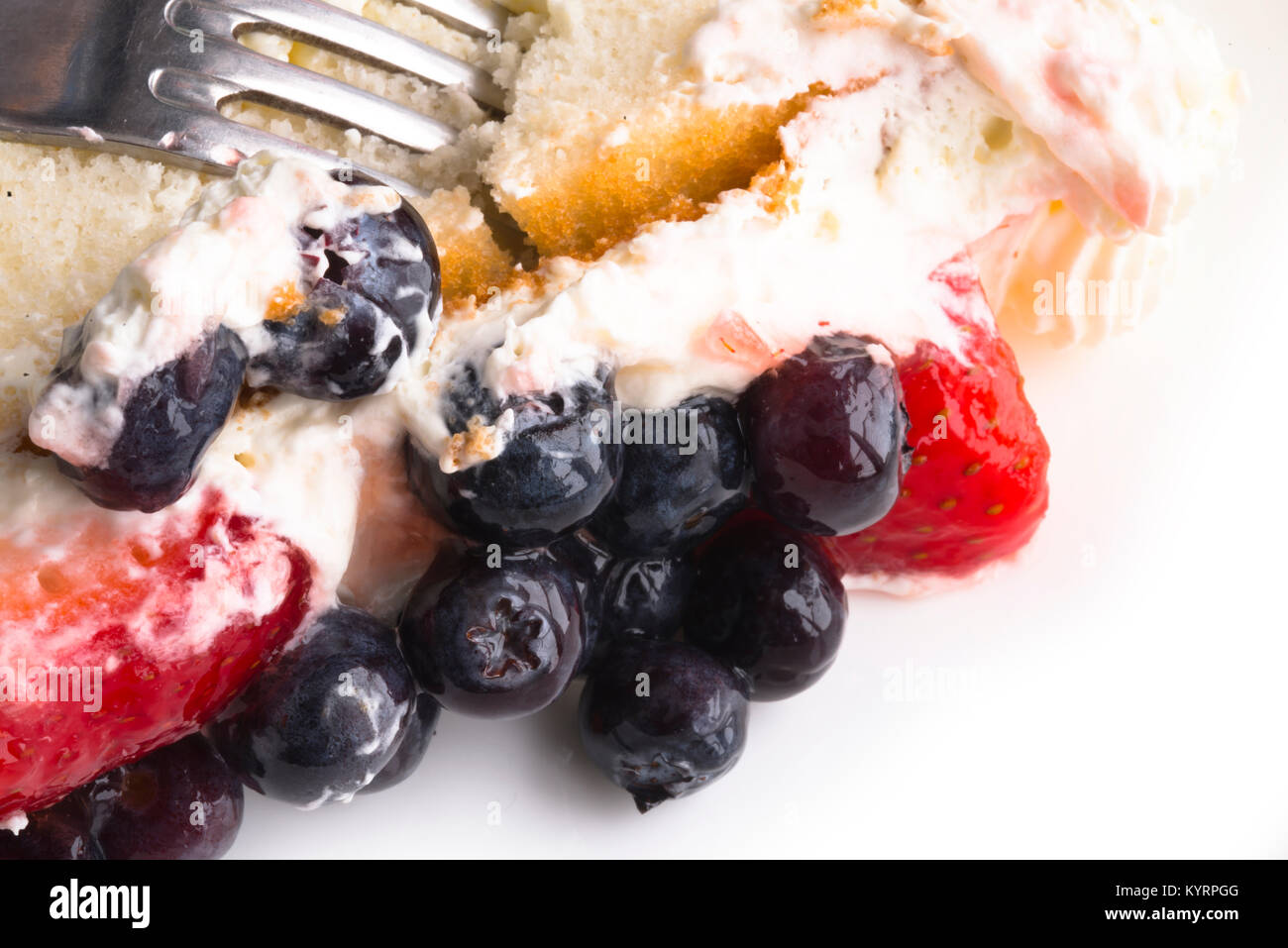 Appetizing fruit cake made of biscuit dough with a delicious sweet cream on which fresh strawberries and blueberries - Stock Image