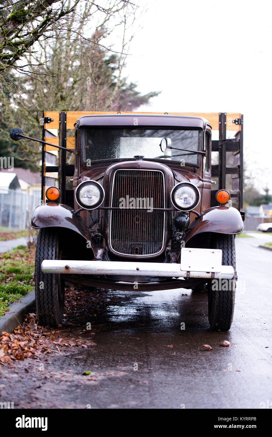 An old rarity rusty shine wet truck in working condition with a vintage design stands on the street under a fence - Stock Image