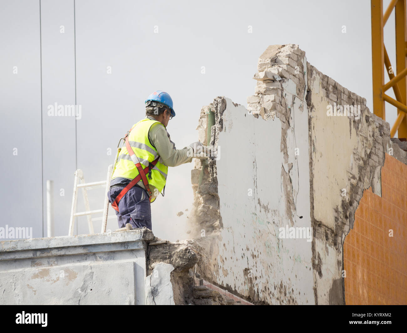 Workman demolishing wall on high building without safety harness being attached. - Stock Image