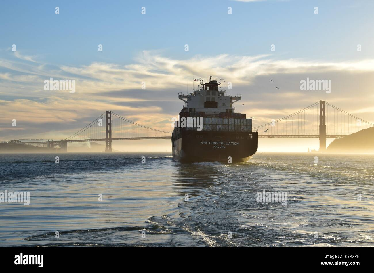 Container ship NYK Constellation leaves San Francisco Bay under the Golden Gate Bridge into the sunset. - Stock Image