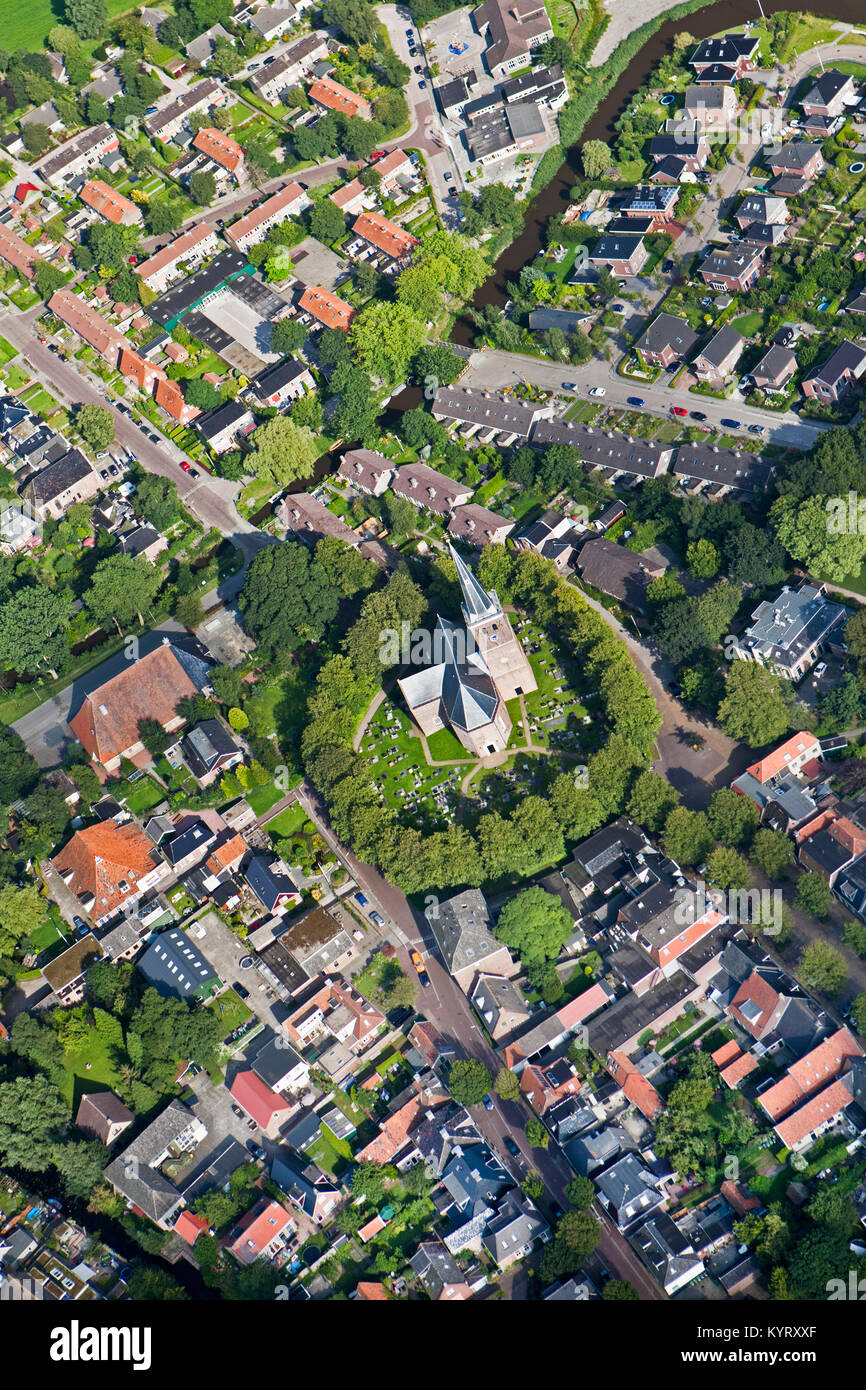 The Netherlands, Wirdum, Center of village. Church constructed on mound, formerly a refuge in times of flooding. Stock Photo