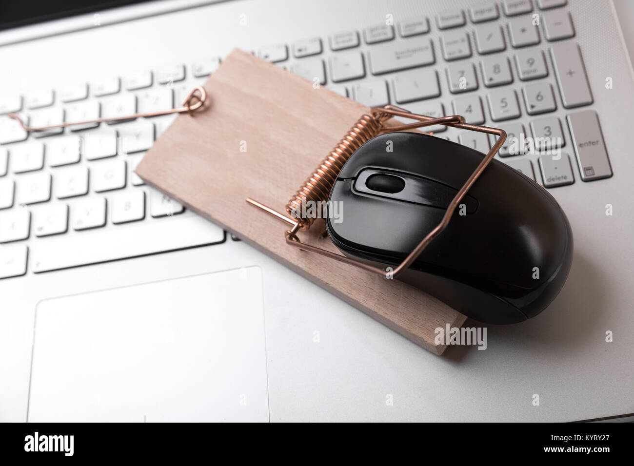 computer mouse in mousetrap on laptop keyboard - censored internet and crime concept - Stock Image