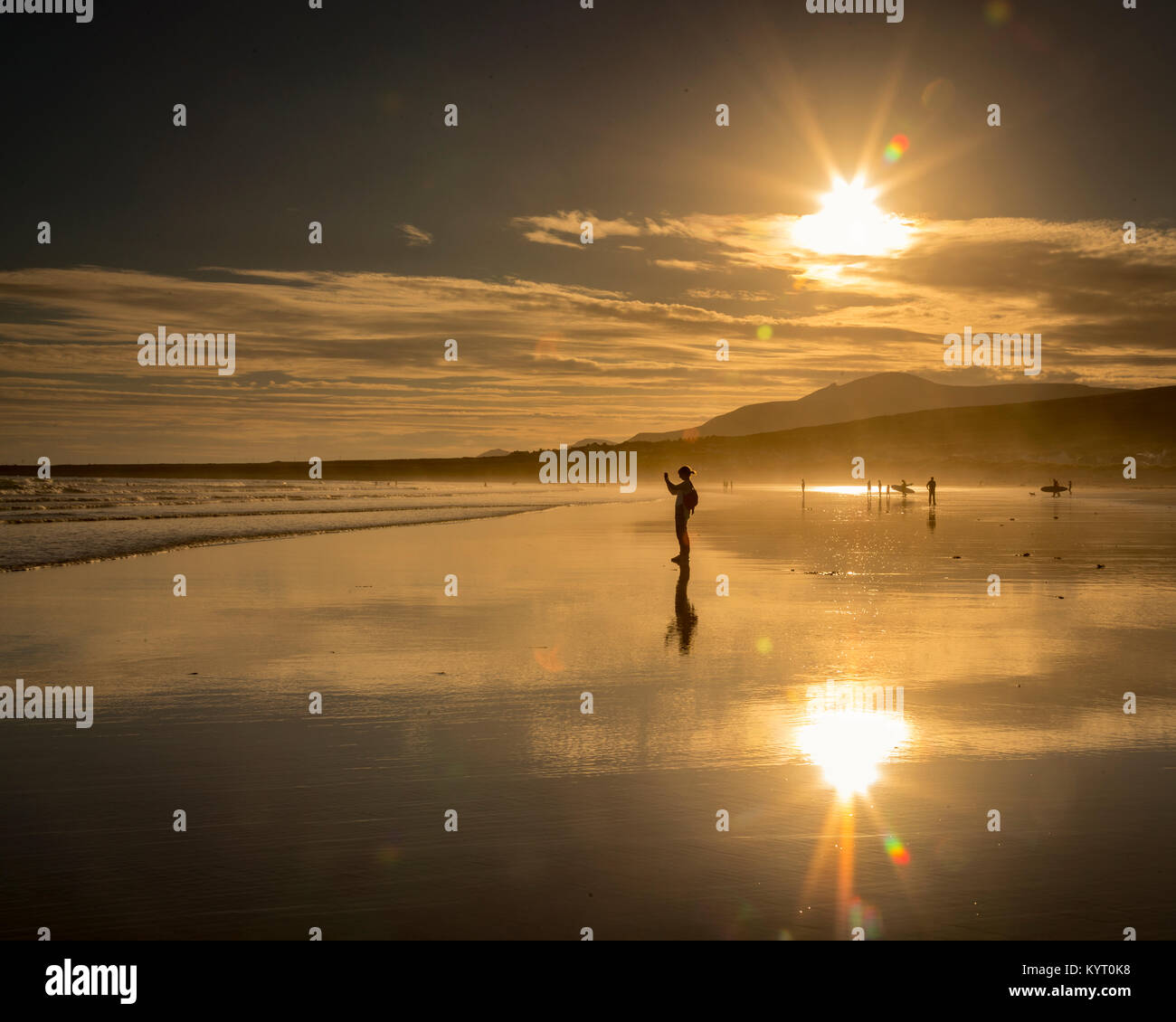 Girl in silhouette taking a photo while standing on reflective wet sand on Keel beach on the west coast of Ireland - Stock Image
