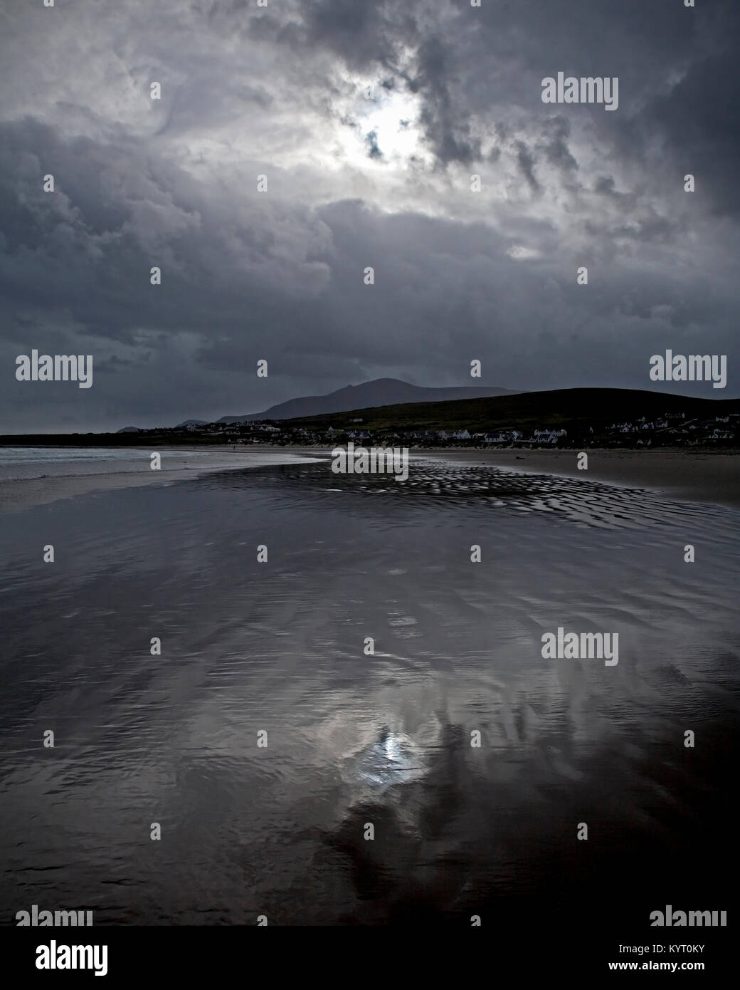 Stormy clouds reflecting in wet sand on the beach at Achill Island on the Irish coast - Stock Image