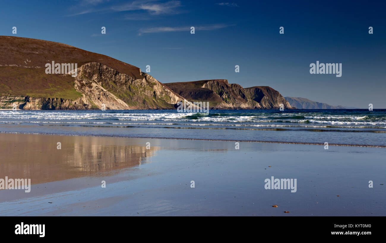 Cliffs reflecting in wet sand on Keel beach, Achill Island, Ireland - Stock Image